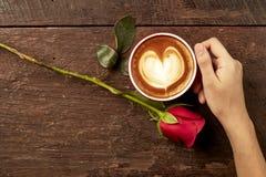 Main d'une jeune femme tenant une tasse de café rouge Photo stock