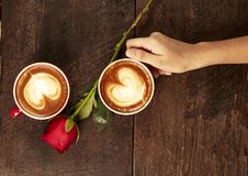 Main d'une jeune femme tenant une tasse de café rouge Photographie stock libre de droits