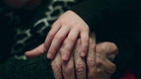 Main d'une petite fille caressant de vieilles mainsd'Â de grand-mère avec amour clips vidéos