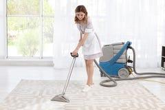 Main-d'œuvre féminine enlevant la saleté du tapis avec l'aspirateur professionnel, à l'intérieur Photos stock