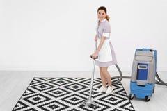 Main-d'œuvre féminine enlevant la saleté du tapis avec l'aspirateur professionnel, à l'intérieur Photographie stock libre de droits