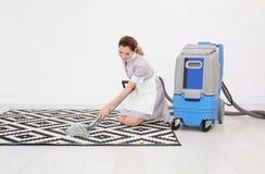 Main-d'œuvre féminine enlevant la saleté du tapis avec l'aspirateur professionnel, à l'intérieur Images stock