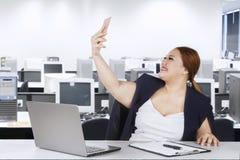 Main-d'œuvre féminine prenant la photo de selfie dans le bureau Photos libres de droits