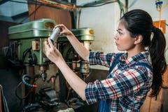 Main-d'œuvre féminine tenant les composants argentés de pièces Images stock