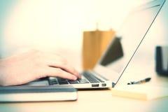 Main dactylographiant du côté d'ordinateur portable Photos libres de droits