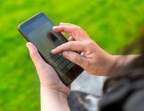 Main dactylographiant sur le téléphone portable Photos libres de droits