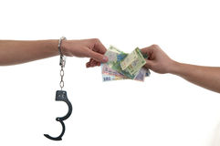 Main dans des menottes donnant l'argent Images libres de droits