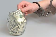 Main dans des menottes prenant l'argent du pot en verre sur le gris Image stock