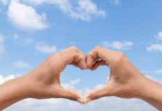 Main dans l'amitié d'amour d'exposition de forme de coeur sur le ciel bleu Photos stock
