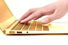 Main dans l'ordinateur portable d'or Photographie stock