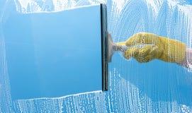 Main dans la fenêtre en caoutchouc jaune de nettoyage de gant sur un ciel bleu Images stock