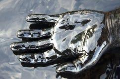 Main dans la flaque de pétrole Photographie stock