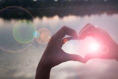 Main dans la forme du coeur d'amour Photos stock