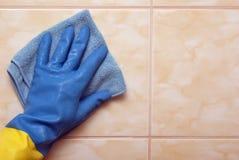 Main dans le bleu avec le gant jaune Photos libres de droits