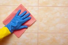Main dans le bleu avec le gant jaune Photo stock
