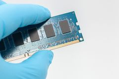 Main dans le gant bleu tenant la mémoire de RAM image libre de droits