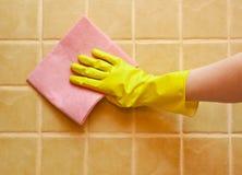 Main dans le gant jaune Photo stock