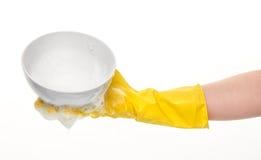 Main dans le gant jaune tenant la cuvette blanche propre dans la mousse Photo stock