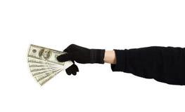Main dans le gant noir tenant l'argent Images libres de droits