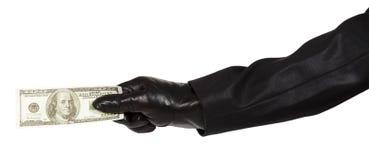 Main dans le gant noir tenant l'argent Photo libre de droits