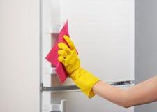 Main dans le réfrigérateur blanc de nettoyage de gant jaune avec du chiffon rose Image stock