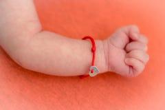 Main de bébé avec le bracelet rouge Image stock