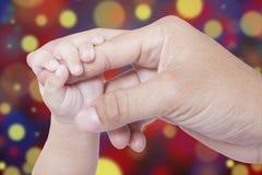 Main de bébé et main de père avec le fond de bokeh Image stock
