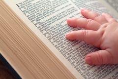 Main de bébé sur la bible ouverte image stock