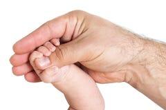 Main de bébé tenant le pouce du parent Images stock