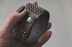 Main de balancier dans le bracelet en cuir Photo stock
