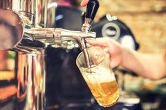 Main de barman au robinet de bière versant une portion de bière blonde d'ébauche dans un restaurant image stock
