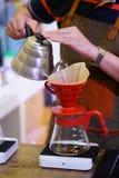 Main de barman versant l'eau chaude dans le fabricant de café d'égouttement photos stock