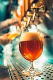 Main de barman versant une grande bière blonde dans le robinet image stock