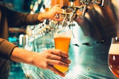 Main de barman versant une grande bière blonde dans le robinet photographie stock libre de droits