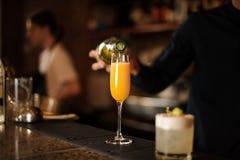 Main de barman versant une orangeade fraîche et lumineuse dans un verre images stock