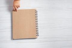 Main de bloc-notes et d'enfant sur une table blanche images libres de droits