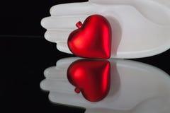 Main de céramique et coeur rouge sur le bureau en verre Photos stock