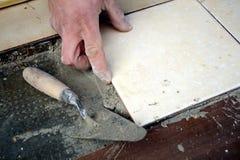 Main de carreleur de maçon étendant une tuile sur l'étage Image libre de droits