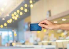 Main de carte de crédit se tenant avec le restaurant brouillé Image stock