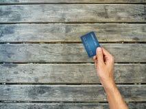 Main de carte de crédit tenant dessus la table en bois Images libres de droits