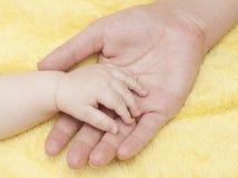 Main de chéri dans la paume de la mère Photo stock