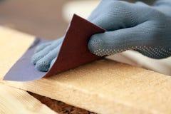 Main de charpentier frottant le conseil en bois Photos libres de droits
