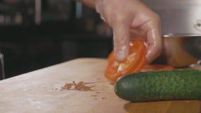 Main de chef coupant en tranches le poivron rouge sur un conseil pour faire cuire le repas banque de vidéos