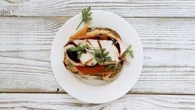 Main de chef faisant le sandwich avec le houmous, la viande de poulet, les verts et le légume grillé pour le petit déjeuner et le clips vidéos
