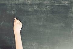 Main de Childs avec la craie sur le tableau noir Photographie stock