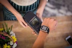 Main de client effectuant le paiement par le smartwatch Image stock
