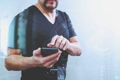 Main de concepteur utilisant le téléphone intelligent pour le shopp en ligne de paiements mobiles Photographie stock