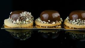 Main de confiseur mise en mini dessert de pâtisserie de mousse de rowfrench couvert de lustre de chocolat clips vidéos