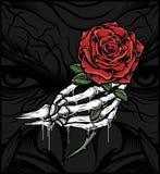 Main de crâne tenant une rose image stock