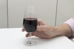 Main de dame âgée tenant un verre de vin Photos stock